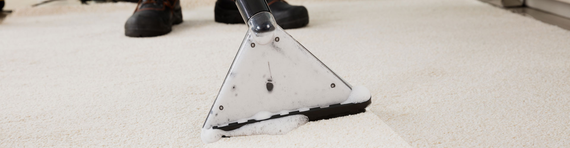 A Person Cleaning Carpet With Vacuum Cleaner